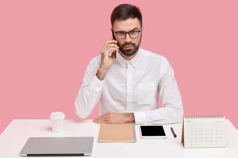 Perfect man sat at a desk. Prides himself on being a perfectionist.