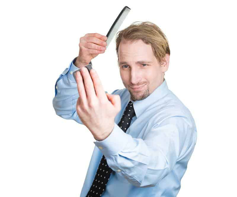 Man looking in mirror trying to look perfect as he is a perfectionist.