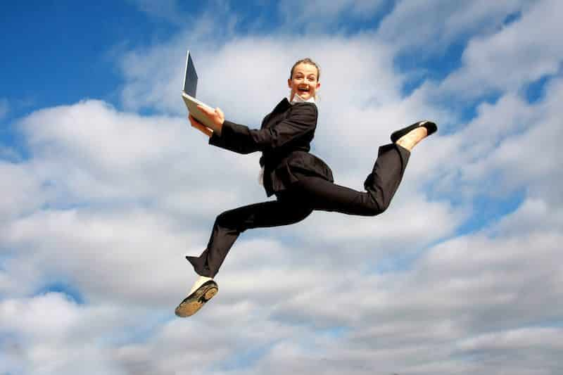Woman jumping for joy holding laptop overcoming perfectionism.