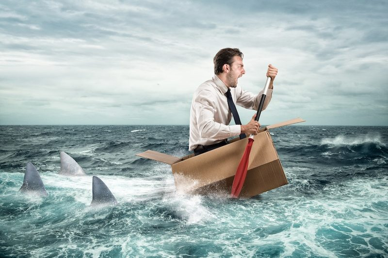 Business man in a cardboard box boat being chased by sharks. He has Sunday night blues - the dread of going into work on a Monday.