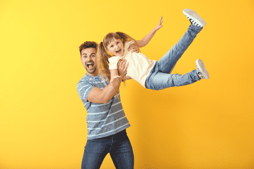 Smiling man holding a child in a fun way. Parenting.