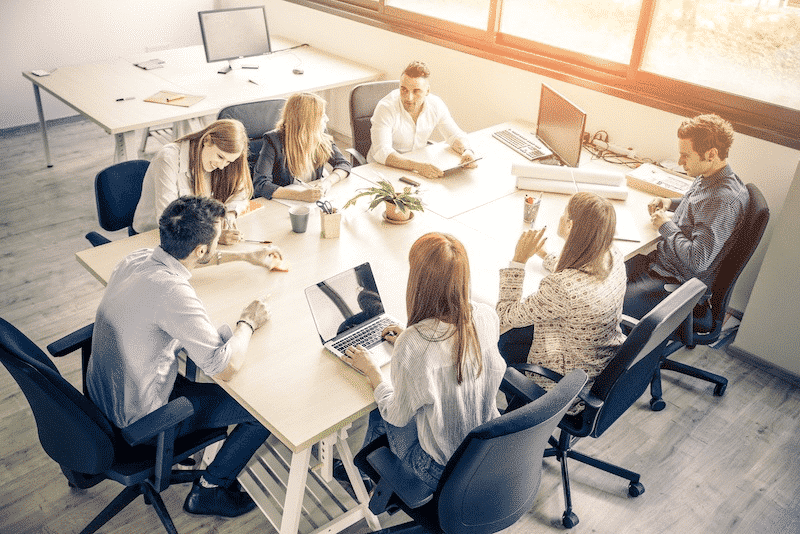 Group of people in a meeting sat a meeting table. How to run a meeting.