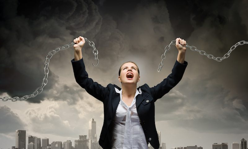 Strong woman with broken chains. Freed from her limiting beliefs.