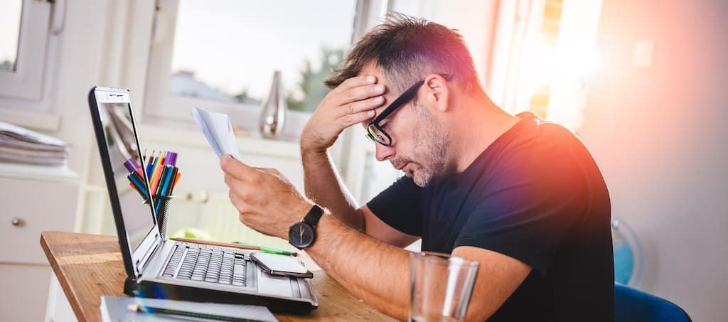 Man sat at a desk worrying, looking stressed