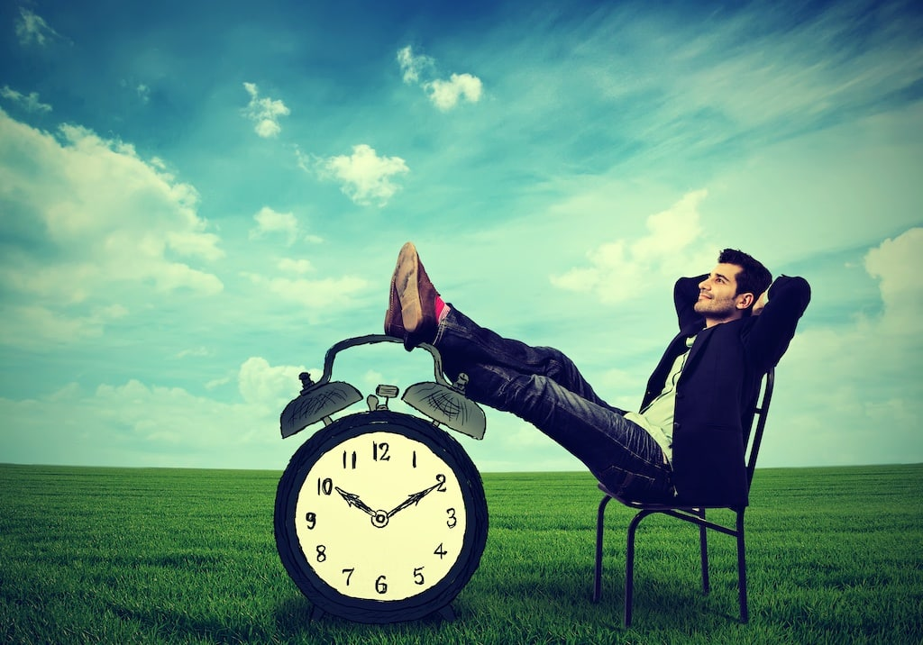 Man relaxing in a chair with his feet on a clock. What is procrastination?